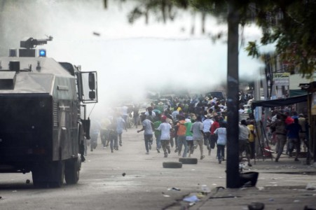 Demonstrators flee from a water cannon during a march against the government of Haitian President Michel Martelly in Port-au-Prince on January 10, 2015 (AFP Photo/Hector Retamal)